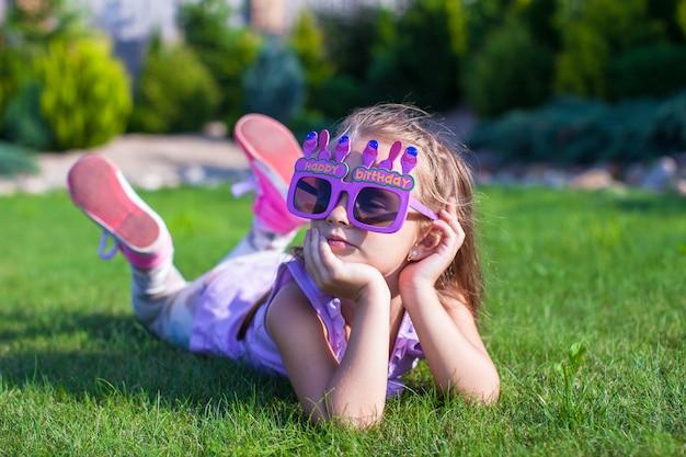 Entzückendes kleines mädchen beim alles- gute zum geburtstagglaslächeln im freien Premium Fotos