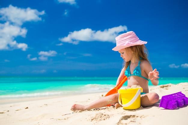 Entzückendes kleines mädchen, das auf dem strand mit weißem sand spielt Premium Fotos
