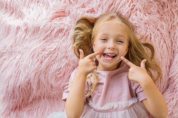 Entzückendes kleines mädchen, das auf rosa pelzdecke liegt Premium Fotos