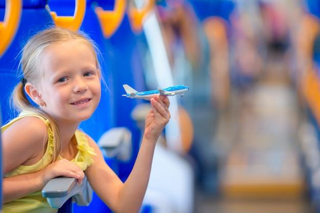 Entzückendes kleines mädchen, das auf zug reist und spaß mit flugzeugmodell in den händen hat Premium Fotos