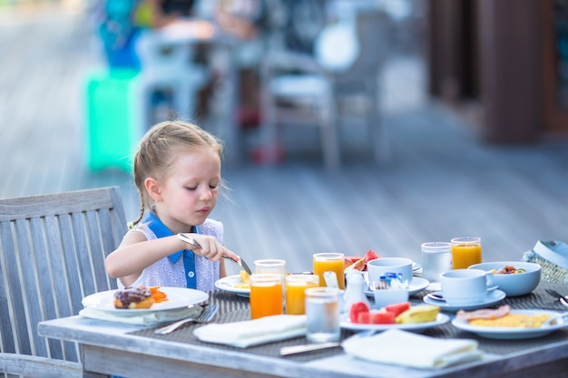 Entzückendes kleines mädchen, das café am im freien frühstückt Premium Fotos