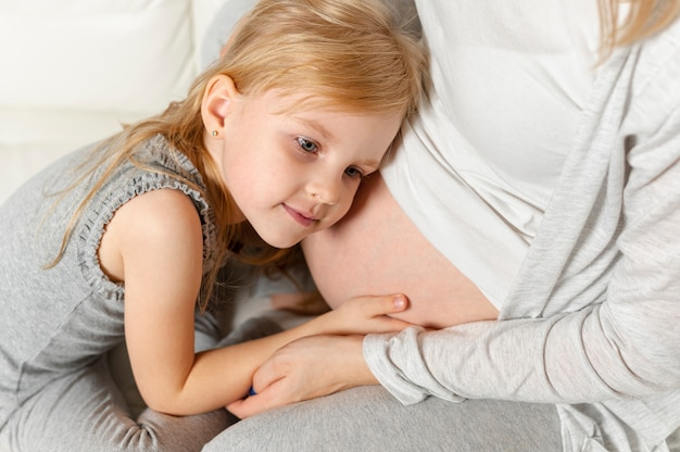 Entzückendes kleines mädchen, das mit dem schwangeren mutterbauch spielt Kostenlose Fotos