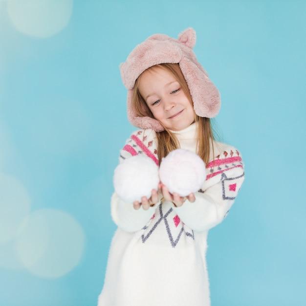 Entzückendes kleines mädchen, das schneebälle hält Kostenlose Fotos