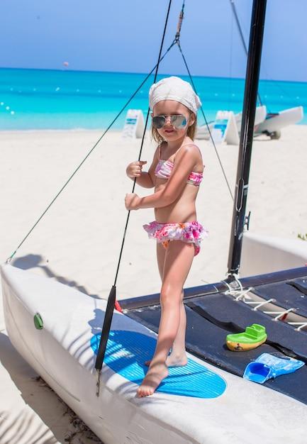 Entzückendes kleines mädchen haben spaß auf einer yacht während der karibischen ferien Premium Fotos