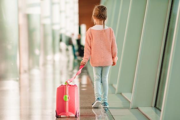 Entzückendes kleines mädchen im flughafen mit ihrem gepäck, das auf einstieg wartet Premium Fotos