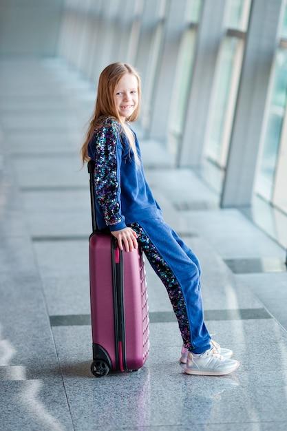 Entzückendes kleines mädchen im flughafen mit ihrem gepäck Premium Fotos