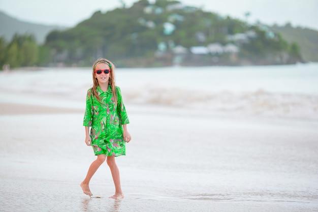 Entzückendes kleines mädchen im großen roten hut auf dem strand Premium Fotos