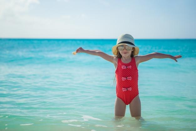 Entzückendes kleines mädchen im hut auf strand während der sommerferien Premium Fotos