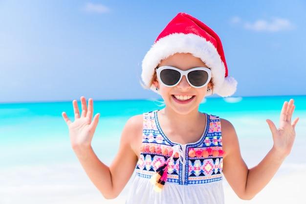 Entzückendes kleines mädchen in sankt-hut während der weihnachtsstrandferien Premium Fotos
