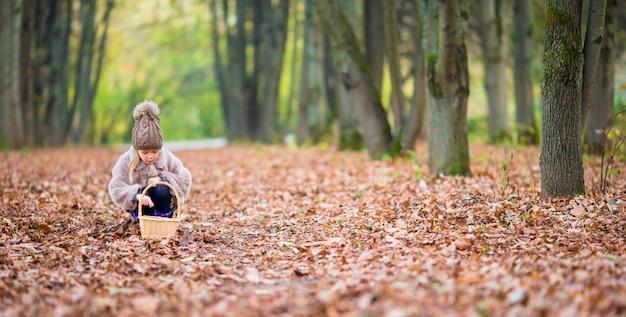 Entzückendes kleines mädchen mit einem korb am herbsttag draußen im schönen wald Premium Fotos