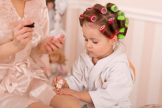 Entzückendes kleines mädchen mit ihrer mutter in lockenwicklern malen ihre fingernägel. kopiert mamas verhalten. mama bringt ihrer tochter bei, auf sich selbst aufzupassen. schönheitstag. Premium Fotos