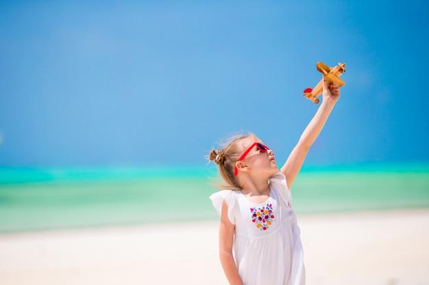 Entzückendes kleines mädchen mit spielzeugflugzeug in den händen auf weißem tropischem strand Premium Fotos