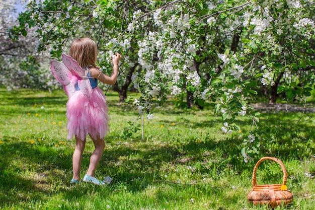 Entzückendes kleines mädchen mit strohkorb in blühendem apfelgarten Premium Fotos