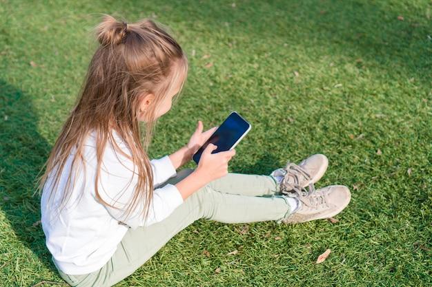 Entzückendes kleines mädchen mit telefon während der sommerferien draußen Premium Fotos