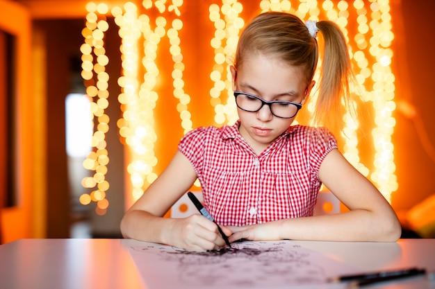 Entzückendes kleines mädchen schreibt santa klaus einen brief, der auf dem tisch sitzt Premium Fotos