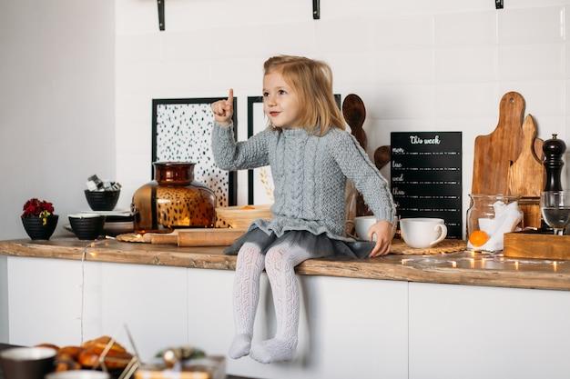 Entzückendes kleines mädchen sitzt auf küchentisch. kleines mädchen in der küche zu hause Premium Fotos