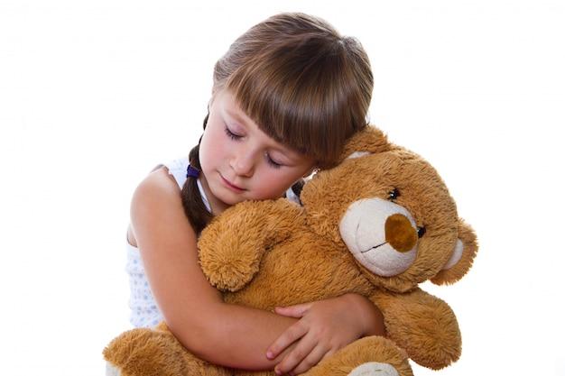 Entzückendes kleinkindmädchen, das einen teddybären umarmt Premium Fotos