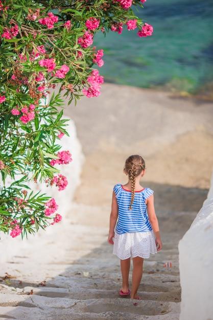 Entzückendes mädchen, das spaß draußen hat. scherzen sie an der straße des typischen griechischen traditionellen dorfs mit weißen wänden und bunten türen auf mykonos-insel, in griechenland Premium Fotos