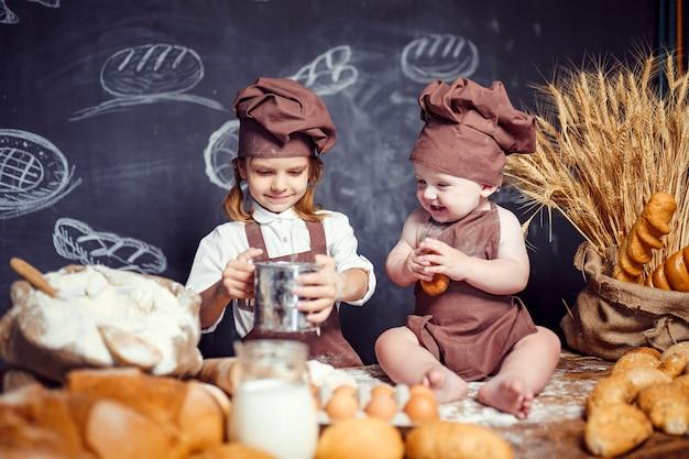 Entzückendes mädchen mit kind auf dem tischkochen Premium Fotos