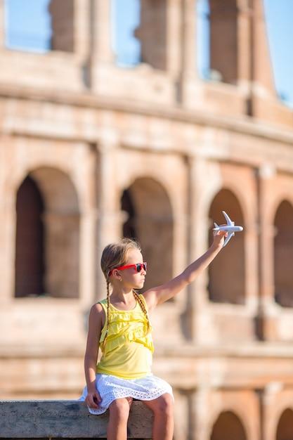 Entzückendes mädchen mit kleinem spielzeugmodellflugzeughintergrund colosseum in rom, italien Premium Fotos