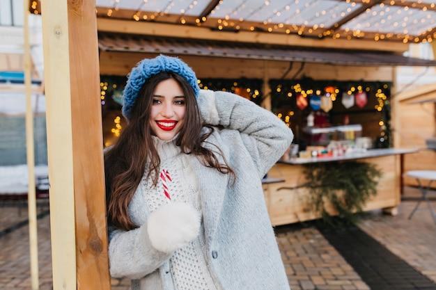 Entzückendes mädchen mit langen braunen haaren, die mit lächeln nahe markt verziert mit weihnachtsgirlande aufwerfen. außenporträt der freudigen europäischen dame im trendigen grauen mantel, der lutscher hält und lacht. Kostenlose Fotos