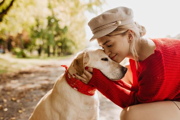 Entzückendes mädchen und ihr hund sitzen unter grünen bäumen und strahlender sonne im park. schöne blondine, die eine gute zeit zusammen mit ihrem haustier hat. Kostenlose Fotos