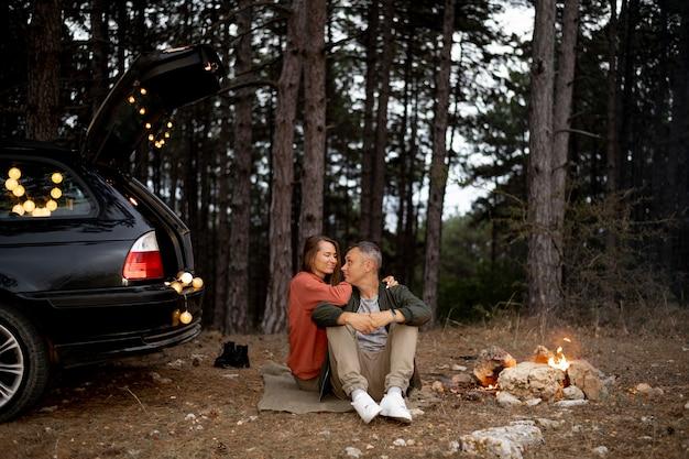 Entzückendes paar, das lagerfeuer genießt Kostenlose Fotos