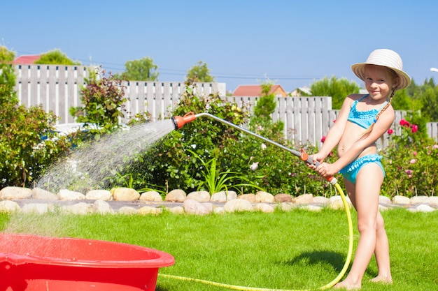 Entzückendes strömendes wasser des kleinen mädchens vom schlauch und vom lachen Premium Fotos
