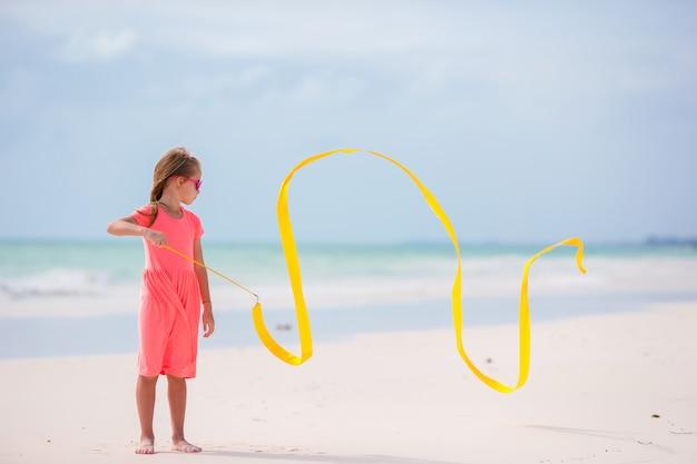 Entzückendes tanzen des kleinen mädchens mit mit gymnastischem band Premium Fotos