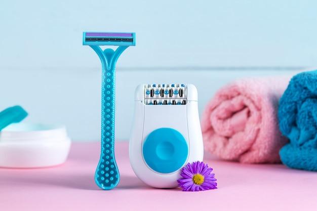 Epilierer, creme, damenrasierer, handtücher und blumen. enthaarungsmittel. entfernung unerwünschter haare. epilationskonzept Premium Fotos