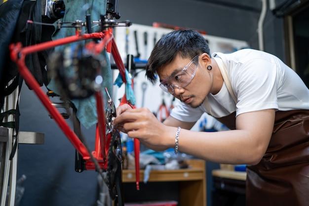 Er benutzt eine tablette, um das produkt zu überprüfen. der eingang des fahrradladens kümmert sich um die fahrräder der kunden, um den zustand zu überprüfen. Premium Fotos