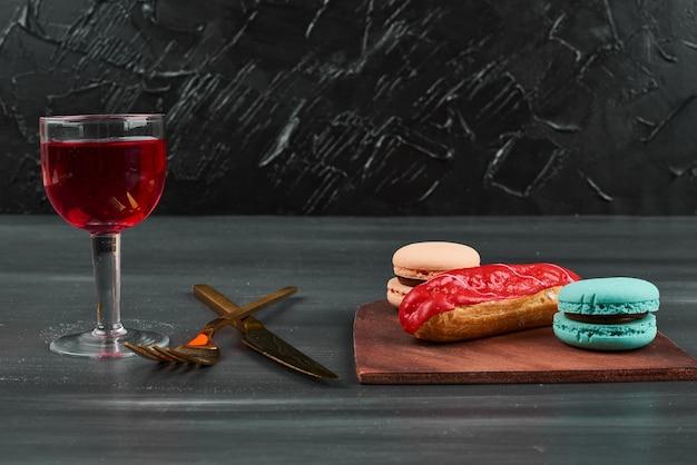 Erdbeer-eclair mit einem glas wein und macarons. Kostenlose Fotos