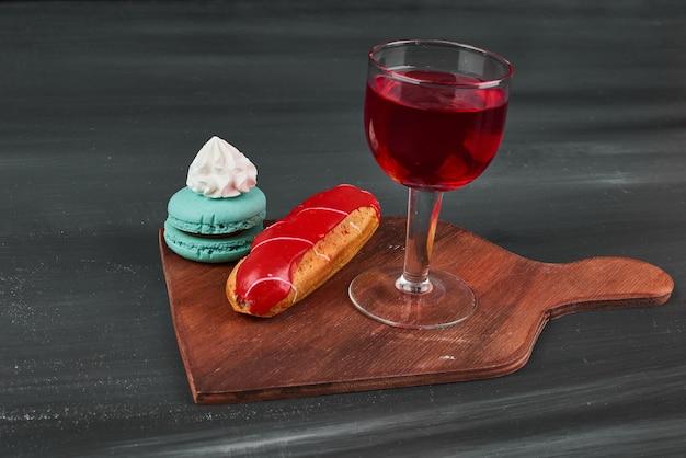 Erdbeer-eclair mit französischen macarons und einem glas wein. Kostenlose Fotos