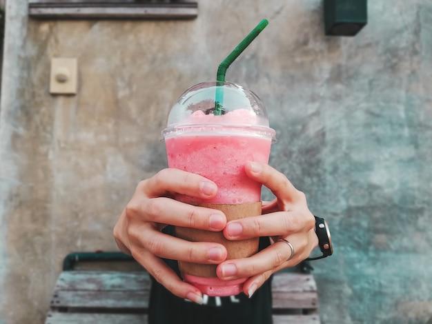 Erdbeer-smoothie in der hand Premium Fotos