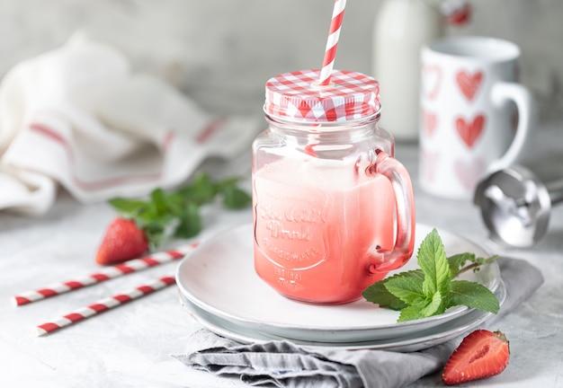 Erdbeer- und milch- oder joghurt-smoothies in einem schönen roten glas und minzzweigen auf einem weißen betontisch. Premium Fotos