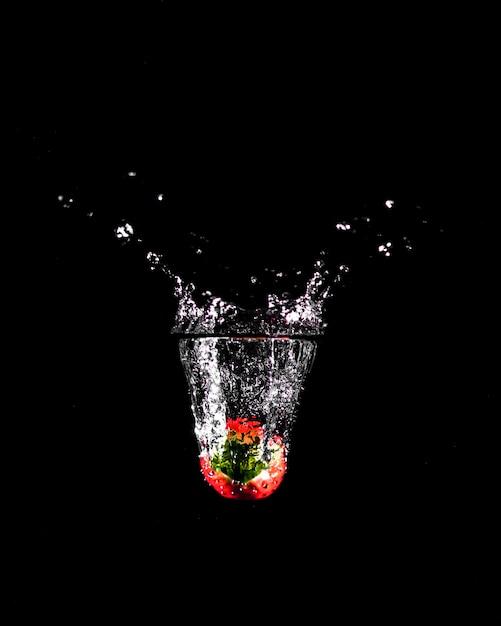 Erdbeere, die in das wasser eintaucht Kostenlose Fotos
