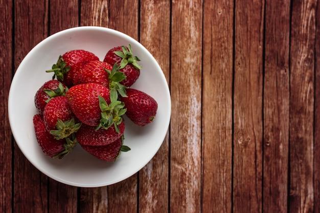 Erdbeeren auf einem teller auf einem holztisch Premium Fotos