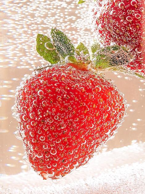 Erdbeeren in einem glasbehälter mit blasen im neontonen mit steigung Premium Fotos