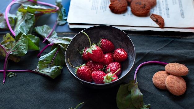Erdbeeren innerhalb der schüssel, der plätzchen, des buches und der blätter auf einer schwarzen matte. Kostenlose Fotos