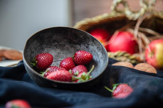 Erdbeeren innerhalb der schüssel, der plätzchen und des apfelkorbes auf einer schwarzen matte, unscharfer korb. Kostenlose Fotos