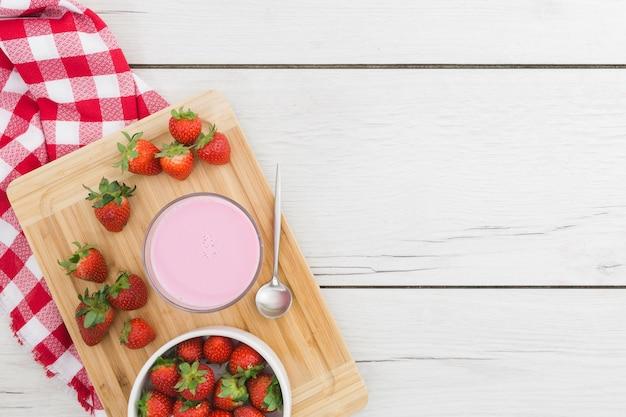 Erdbeeresmoothie auf hölzernem brett mit früchten Kostenlose Fotos