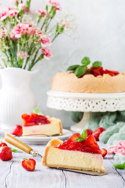 Erdbeerkäsekuchen und blumen Premium Fotos