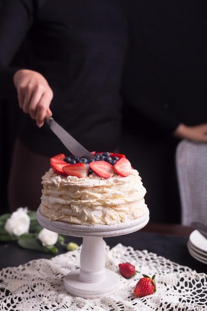 Erdbeerpavlova-kuchen verziert von der frau Premium Fotos