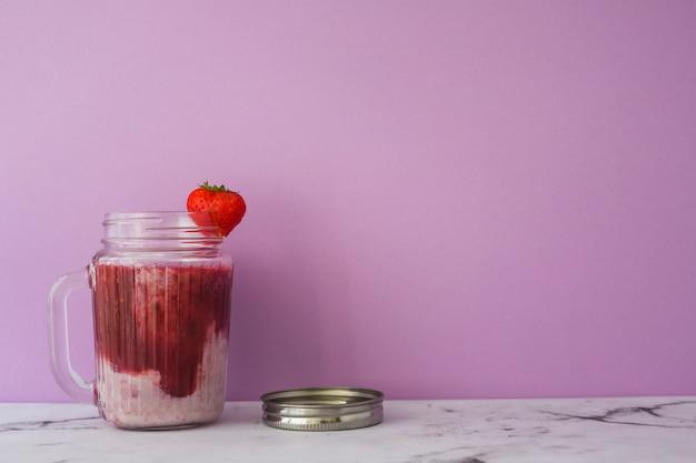 Erdbeersmoothie im glas gegen rosa hintergrund Kostenlose Fotos