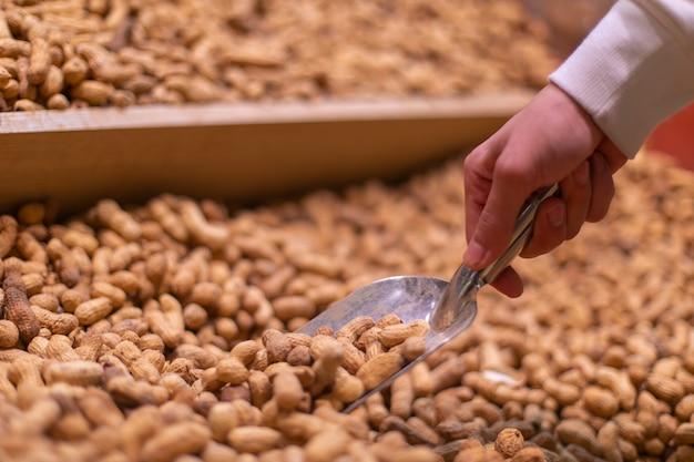 Erdnüsse aus dem vorrat im supermarkt nehmen. hochwertiges foto Kostenlose Fotos