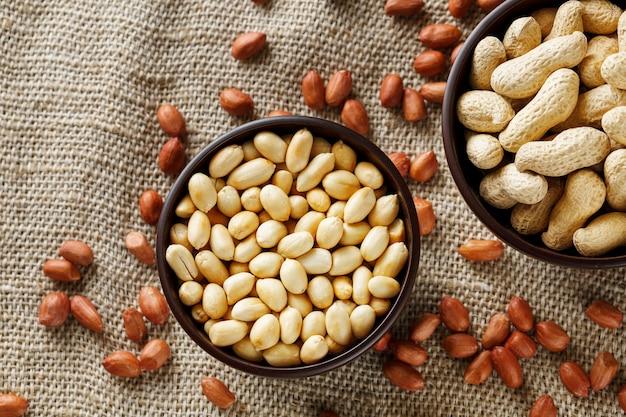 Erdnüsse im oberteil und in der abgezogenen nahaufnahme in einer schale Premium Fotos