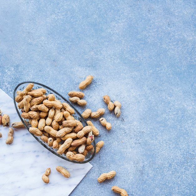 Erdnüsse in der glasschüssel auf rauem strukturiertem hintergrund Kostenlose Fotos