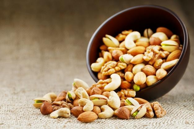 Erdnüsse in der schale und geschälte nahaufnahme in tassen Premium Fotos