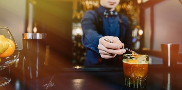 Erfahrener barmixer, der cocktail an der bar macht Premium Fotos