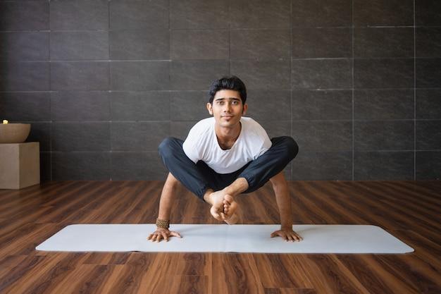 Erfahrener jogi, der leuchtkäferhaltungsänderung in der turnhalle tut Kostenlose Fotos